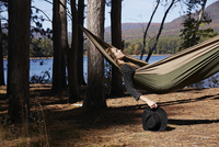 A woman lying in a hammock relaxing, under the pine trees by a lake. 11093013596| 写真素材・ストックフォト・画像・イラスト素材|アマナイメージズ