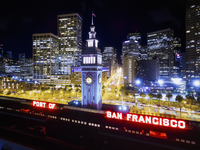 The view over the Ferry building, the clock tower and sign saying The Port of San Francisco at night.