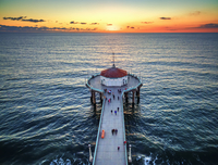 Aerial view of the Manhattan Beach Pier at sunset.