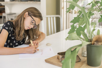A young girl wearing glasses working at a table, using a pen, writing and drawing.