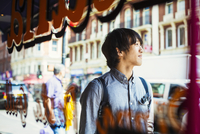 Young Japanese man enjoying a day out in London, walking past a shop window. 11093013820| 写真素材・ストックフォト・画像・イラスト素材|アマナイメージズ