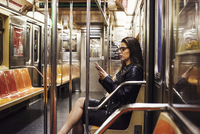 A woman sitting in a metro subway carriage looking at her cellphone.