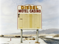 A large roadside sign in a flat landscape with light snow. Mountain range. Diesel and Motel Casino.