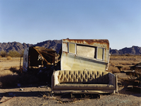 A ruined caravan, with rusting roof, a shelter, and a sofa.
