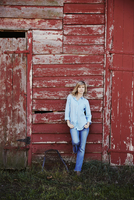 A young woman in jeans leaning against a red painted barn building. 11093014118| 写真素材・ストックフォト・画像・イラスト素材|アマナイメージズ