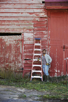 A young man in working clothes and cap carrying a ladder across a farm yard.
