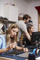 A man standing behind two women sitting working on circuitry in a technology lab.
