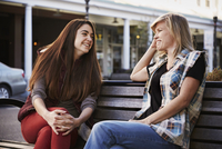 Two women sitting on a bench in an urban environment talking.
