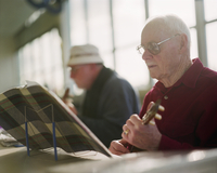 Two elderly men playing ukulele instruments in a senior center.