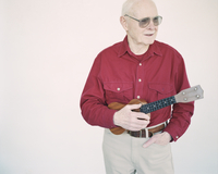 An elderly man in a red shirt holding a ukulele.