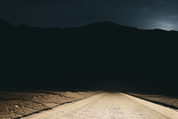 Dirt road in desert illuminated by car headlights, Death Valley National Park, USA, with moonlight in distance. 11093014252| 写真素材・ストックフォト・画像・イラスト素材|アマナイメージズ