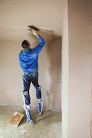 A plasterer wearing stilts smoothing fresh plaster high up on the walls of a house under construction. 11093014422| 写真素材・ストックフォト・画像・イラスト素材|アマナイメージズ