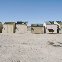 Row of garbage and recycling containers in desert