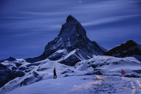 A person walking in a snowy mountainous landscape, with moonlight reflecting off the snow.