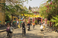 Rear view of people riding their bicycles towards a temple on a city street. 11093014600| 写真素材・ストックフォト・画像・イラスト素材|アマナイメージズ