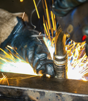 Close up of a metalworker using a tool with sparks flying.