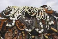 Close up of a pile of tangled up commercial fishing nets with floats attached.