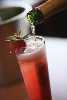 Champagne being poured into a glass garnished with a strawberry. A fruit cocktail.