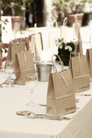 A table outside laid with cutlery and paper bags for party favours.