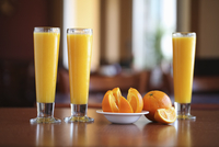 Three glasses of orange juice on a table with a whole and a sliced orange. 11093014664| 写真素材・ストックフォト・画像・イラスト素材|アマナイメージズ