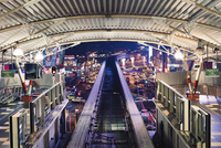 An urban subway station and elevated train tracks lit up at night.
