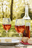 Two wine glasses and a bottle of rose, with cheese and bread on a table outside. 11093014694| 写真素材・ストックフォト・画像・イラスト素材|アマナイメージズ