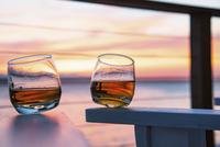 Two glasses of whisky against an ocean sunset.