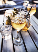 Wine glass and jug of cocktails with glass of water on a table outside.