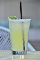 A margarita cocktail with a straw and a lime wedge on a table outside.