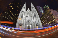 A fish-eye lens of St Patrick's Cathedral in New York with light trails from traffic, building lit up at night. City life.