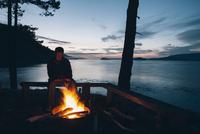 Man sitting by campfire at dusk, San Juan Islands in the distance, Washington, USA. 11093014756| 写真素材・ストックフォト・画像・イラスト素材|アマナイメージズ