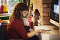 A woman seated with a baby on her lap using her computer, both watching the screen. 11093014792| 写真素材・ストックフォト・画像・イラスト素材|アマナイメージズ