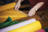 A woman using a tape measure to measure yellow fabric for cutting out. 11093014797| 写真素材・ストックフォト・画像・イラスト素材|アマナイメージズ