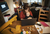 A woman seated with her baby on her lap, multitasking and using a laptop. 11093014810| 写真素材・ストックフォト・画像・イラスト素材|アマナイメージズ