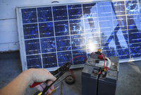 A person attaching a battery to a solar panel.