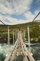 A backpacker walking on a rope bridge across a fast flowing river. 11093014865  写真素材・ストックフォト・画像・イラスト素材 アマナイメージズ