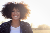 A young woman with an afro hairdo smiling at the camera, outdoors.