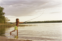 A young girl standing in the shallow water of a lake fishing with a rod.