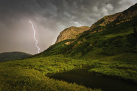 A lightning storm over river running through a mountainous valley. Fork of lightening emerging from clouds. 11093015207| 写真素材・ストックフォト・画像・イラスト素材|アマナイメージズ