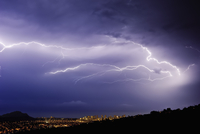 A lightning storm over a city in a valley. Forks of lightening emerging from clouds. 11093015228| 写真素材・ストックフォト・画像・イラスト素材|アマナイメージズ