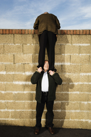 Rear view of man wearing a suit, standing on the shoulders of a man, climbing over yellow brick wall. 11093015298| 写真素材・ストックフォト・画像・イラスト素材|アマナイメージズ