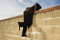 Side view of man wearing a suit climbing over yellow brick wall. 11093015299| 写真素材・ストックフォト・画像・イラスト素材|アマナイメージズ