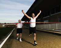 Two men in sportswear running towards the finish line of a race track. 11093015306| 写真素材・ストックフォト・画像・イラスト素材|アマナイメージズ