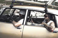 Two men in a vintage car with a surfboard on the roof, man on back-seat with cigarette in his mouth, holding a beer bottle, tatt 11093016719| 写真素材・ストックフォト・画像・イラスト素材|アマナイメージズ