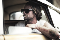 Man with moustache sitting in car, wearing sunglasses, smoking a cigarette, tattooed arm leaning out of window. 11093016720| 写真素材・ストックフォト・画像・イラスト素材|アマナイメージズ