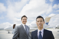 Portrait of businessmen on tarmac with corporate jet