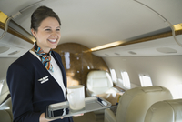 Flight attendant with coffee cup on corporate jet 11096000584| 写真素材・ストックフォト・画像・イラスト素材|アマナイメージズ