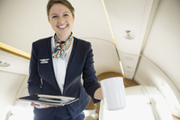 Flight attendant serving coffee on corporate jet