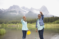 Portrait of sisters holding small fish in lake
