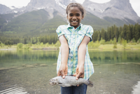 Portrait of proud girl holding fish at lake